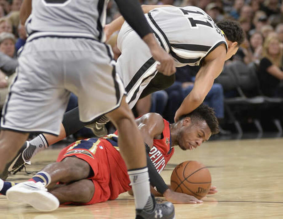 New Orleans Pelicans guard Buddy Hield falls while chasing the ball against San Antonio Spurs guard Bryn Forbes (11) during the first half of an NBA basketball game, Saturday, Oct. 29, 2016, in San Antonio. (AP Photo/Darren Abate)