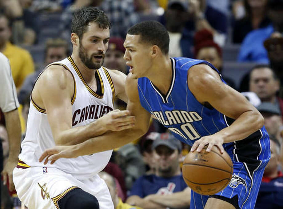 Orlando Magic forward Aaron Gordon (00) drives on Cleveland Cavaliers forward Kevin Love (0) during the first half of an NBA basketball game Saturday, Oct. 29, 2016, in Cleveland. (AP Photo/Ron Schwane)
