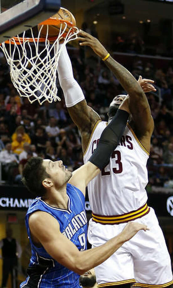 Cleveland Cavaliers forward LeBron James (23) dunks over Orlando Magic center Nikola Vucevic (9) during the first half of an NBA basketball game Saturday, Oct. 29, 2016, in Cleveland. (AP Photo/Ron Schwane)