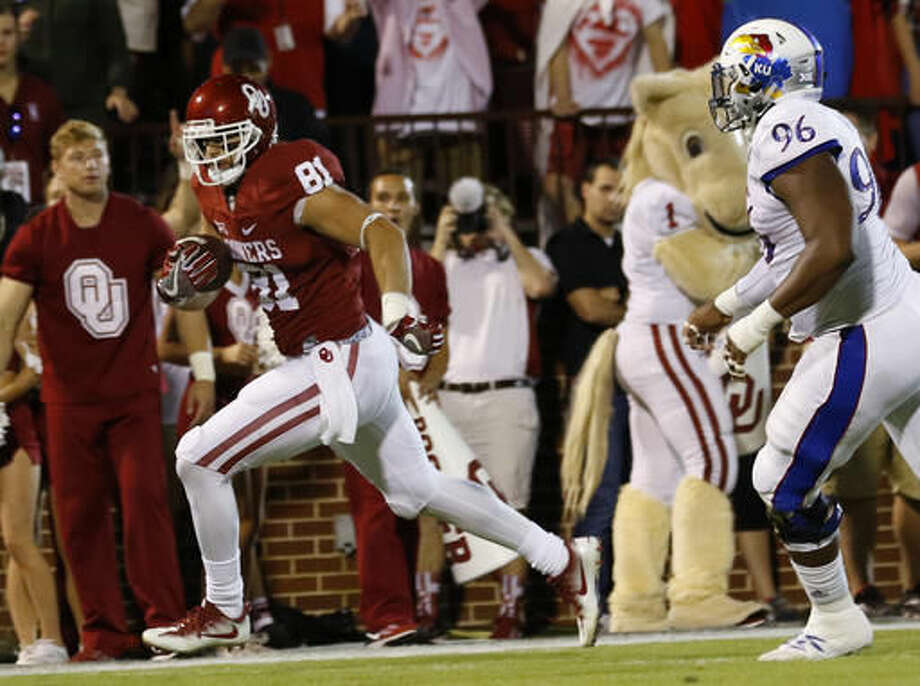Oklahoma wide receiver Mark Andrews (81) runs for a touchdown ahead of Kansas defensive tackle Daniel Wise (96) during the first half of an NCAA college football game in Norman, Okla., Saturday, Oct. 29, 2016. (AP Photo/Alonzo Adams)