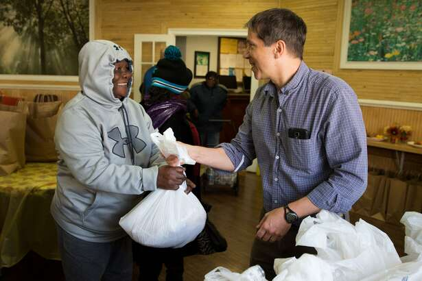 Bill Lattimer, a volunteer from the First Congregational Church in Darien, hands out a turkey at the Open Door Shelter in Norwalk, Conn. on Tuesday, November 22, 2016. In addition to the 160 turkeys that were donated by Stew Leonards for Thanksgiving, recipients also received a bag on non-perishable goods.