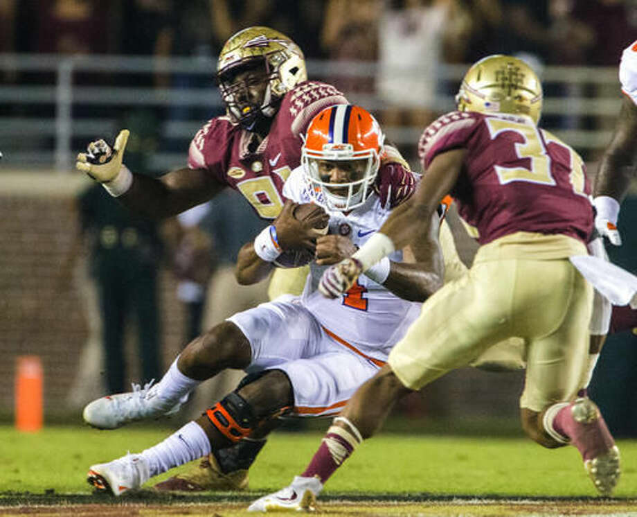 A scrambling Clemson quarterback Deshaun Watson (4) is stopped by Florida State's Kyle Meyers (37) and Derrick Nnadi during the first half of an NCAA college football game in Tallahassee, Fla., Saturday, Oct. 29, 2016. (AP Photo/Mark Wallheiser)