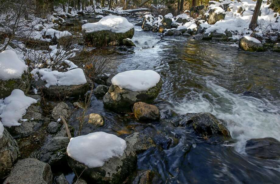 Left: The Stanislaus River flows past rocks covered with snow Thursday in Tuolumne County. Photo: Michael Macor, The Chronicle