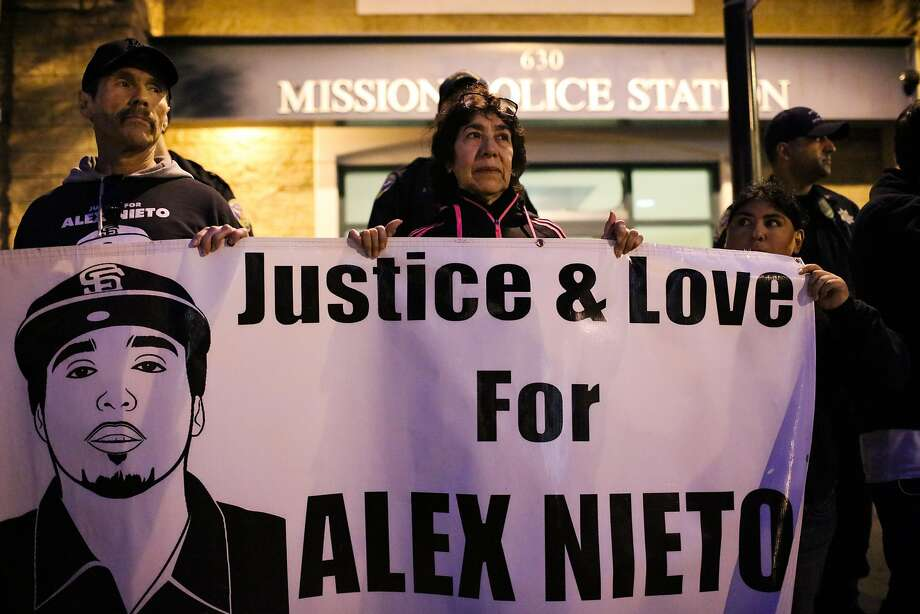 Al Osorio (left) and Elvira Nieto (center), holds a banner in memory of her Elvira's son Alex Nieto, during a march on Valencia Street, where people gathered to mark the one-year anniversary of the death of Amilcar Perez-Lopez, in San Francisco, California, on Friday, February 26, 2016. Photo: Gabrielle Lurie / The Chronicle