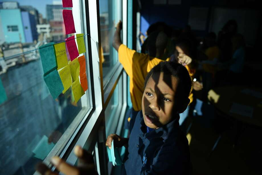 Nine-year-old Phillip Lucas places his stickies on the window of his class room during a class session on the history on Jamestown at Two Rivers Elementary School in Washington, D.C. Two Rivers has the longest waiting list of any charter school in the city -- with almost 1,400 children waiting for a spot in pre-school through eighth grade.  Photo: The Washington Post/Getty Images