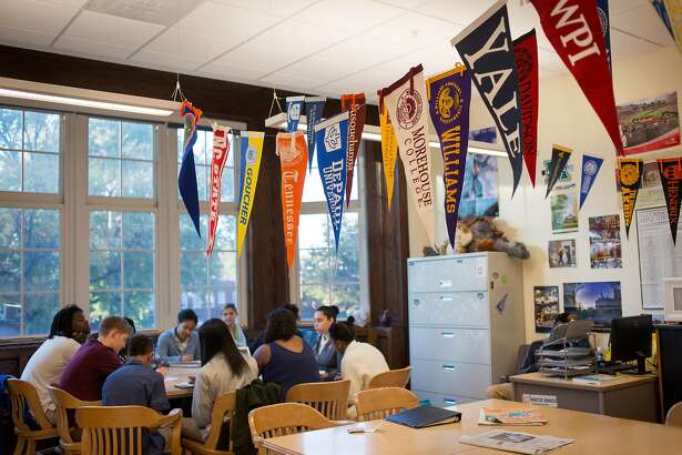 WASHINGTON, DC - OCTOBER 23: College banners hang in the classroom of teacher Chrys Latham, as she leads a senior advisory period, at Washington Latin Public Charter School, in Northwest Washington, D.C., October 23, 2015. The school has a mission of including diverse families, but it has served a lower and lower share of low-income families over time as its performance and reputation have climbed. This year, the school is offering bus transportation to students in Anacostia as a way to boost diverse enrollment. (Photo by Allison Shelley/For The Washington Post via Getty Images)