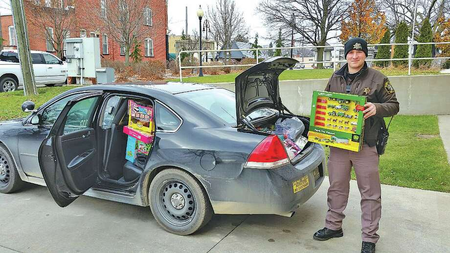 Huron County Sheriff's Office Deputy Gabe Callender helps load a car with donated presents. (Submitted Photo) Photo: Submitted Photo
