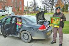 Huron County Sheriff's Office Deputy Gabe Callender helps load a car with donated presents. (Submitted Photo)