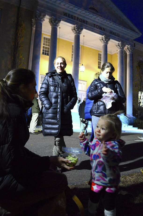 Alexis Lawton of Westport gives her daughter, Nora, 1, a snack before the annual tree lighting at Westport Town Hall, Thursday, Dec. 1, 2016, in Westport, Conn. Photo: Jarret Liotta / For Hearst Connecticut Media / Westport News Freelance