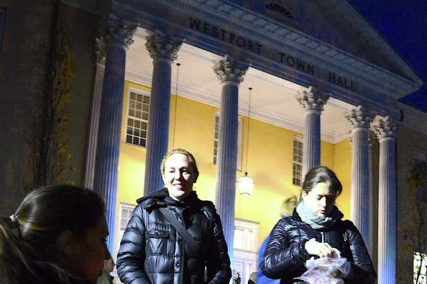 Alexis Lawton of Westport gives her daughter, Nora, 1, a snack before the annual tree lighting at Westport Town Hall, Thursday, Dec. 1, 2016, in Westport, Conn.