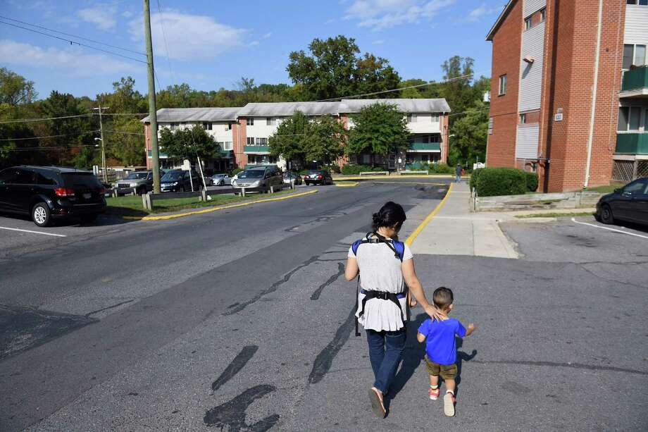 Lisa So carries her son, Felix, 9 months, while walking with her other son, Xavier, 2, at Parkview Gardens Apartments. / The Washington Post