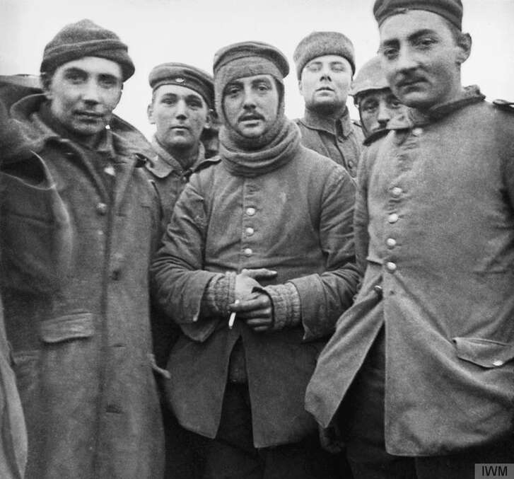 German and British soldiers stand together on the battlefield near Ploegsteert, Belgium, during an impromptu truce in December 1914.