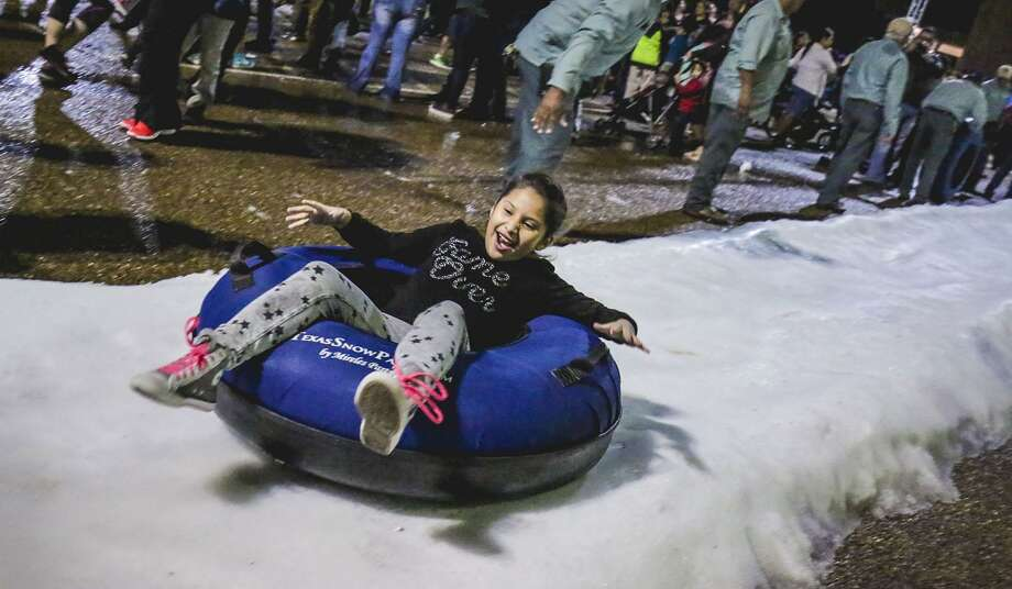 Chloe Tovar reacts as she sleds down a snow slope during the 2016 Navidad Fest. Photo: Victor Strife /Laredo Morning Times