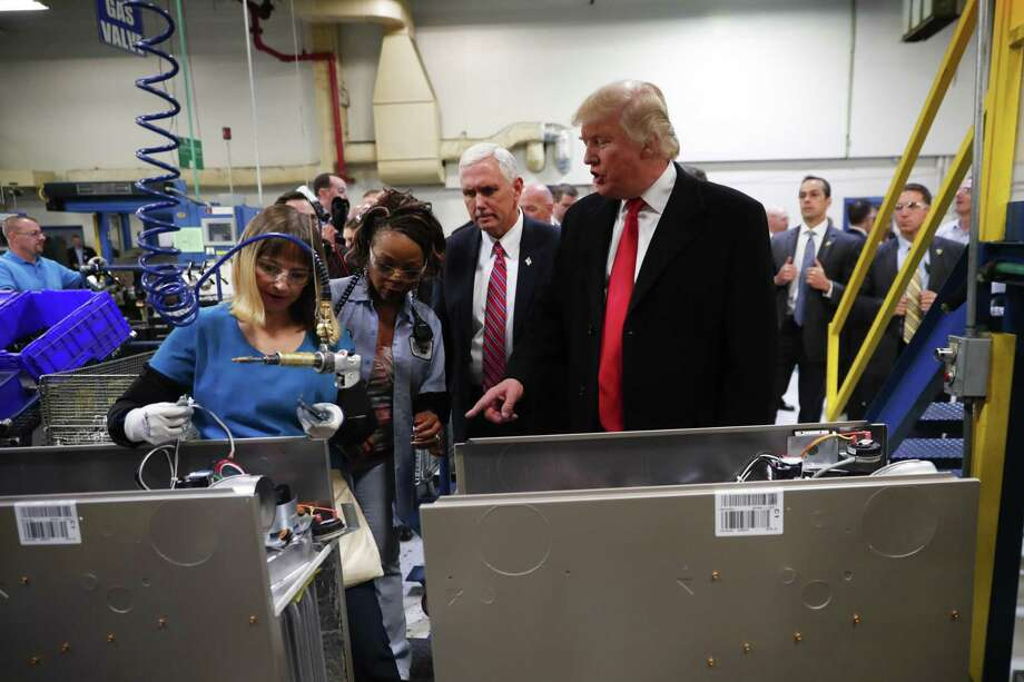 President-elect Donald Trump and Vice President-elect Mike Pence tour a Carrier plant in Indianapolis, Dec. 1, 2016. Trump claimed he could maintain at least 1,100 of those jobs in the U.S. But on Monday, the company gave official notice to that it would start laying off workers on July 20 and keep slashing staff until approximately 800 employees remain. Photo: New York Times File Photo / NYTNS