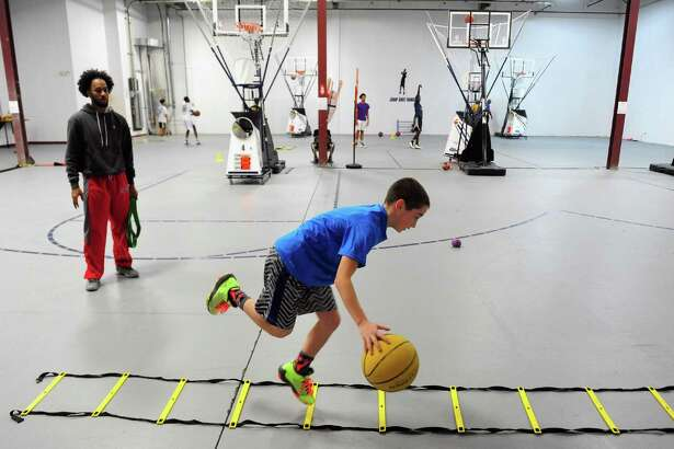 Coach Kwame Burwell watches as student Ty Levine, 11, of Westport, does footwork drills at Jump Shot Range on Access Road in Stratford, Conn. on Saturday Nov. 30, 2016. The newly opened basketball range features five shooting guns, ball handling drills, speed and agility as well as strength and conditioning training.