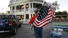 John Purnell unfurls a flag at VFW Post 76 before a group run on Wednesday, Nov. 30, 2016. Purnell has been a fixture in San Antonio's running scene for decades. Purnell, a retired Army veteran, began running on the advice of a doctor for a heart issue while still in the military. He ran his first race while stationed in Hawaii and has never looked back. Purnell later opened a running store, Runaway, near Breckenridge Park. He has also overseen several running events in the city and worked with city leaders in reviving the San Antonio Marathon. Despite the store going out of business, Purnell continues to be part of the running community with Team Red, White and Blue which gathers runners, many who are veterans, for group runs. (Kin Man Hui/San Antonio Express-News)