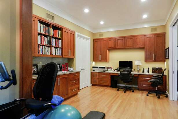 This multifunctional home office with exercise area is by Craftsmanship by John, Inc.