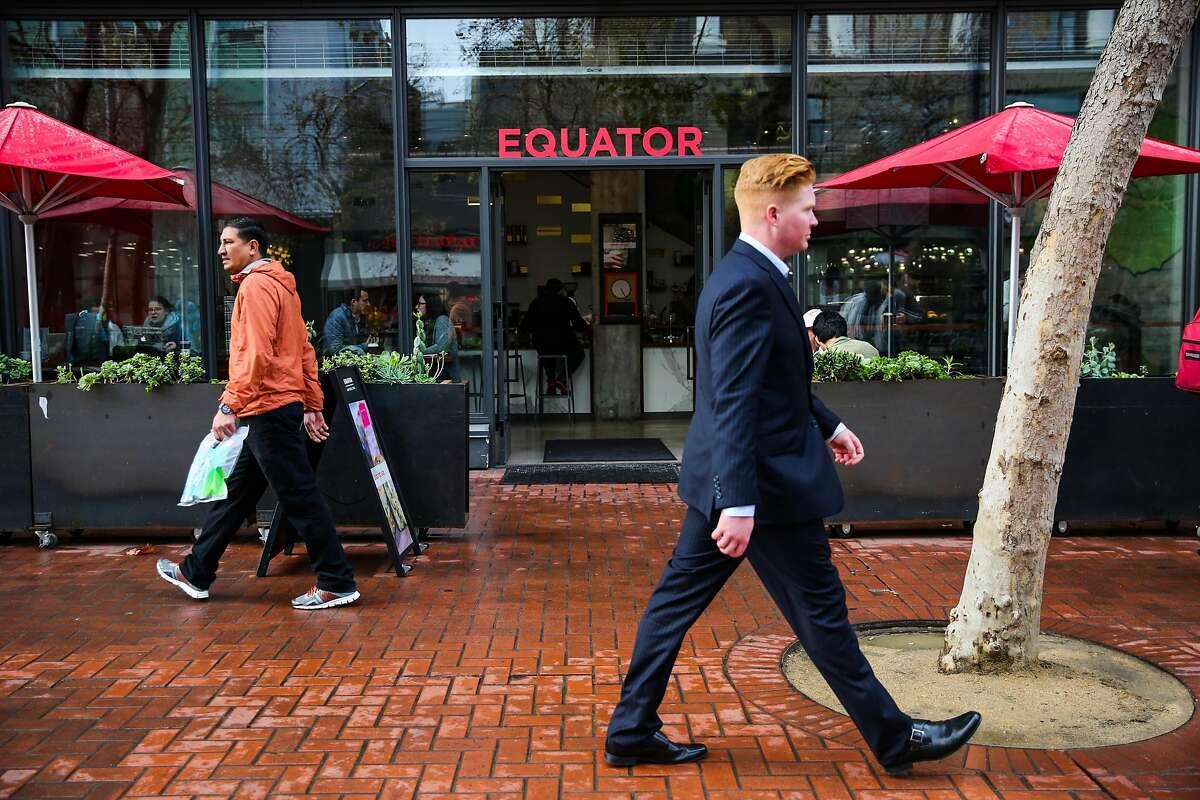 People walk past Equator coffee, on Market Street, in San Francisco, California, on Wednesday, November 30, 2016.