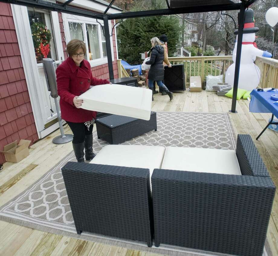Barbara Vincent, Make-A-Wish Manager, puts cushions on new furniture for the deck Eddie Nielsen, 15 of New Fairfield, wished for and the Make-A-Wish Foundation made it possible. Thursday, Dec. 1, 2016 Photo: Scott Mullin / For Hearst Connecticut Media / The News-Times Freelance
