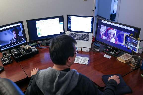 Francis Kong watches TV shows in between working on two out of the six screens he has set up in his home office on Friday, December 2, 2016 in Alameda, Calif.