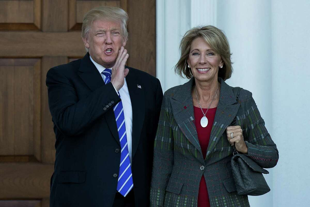 President-elect Donald Trump and Betsy DeVos pose for a photo after their meeting at Trump International Golf Club, Nov. 19, in Bedminster Township, New Jersey.