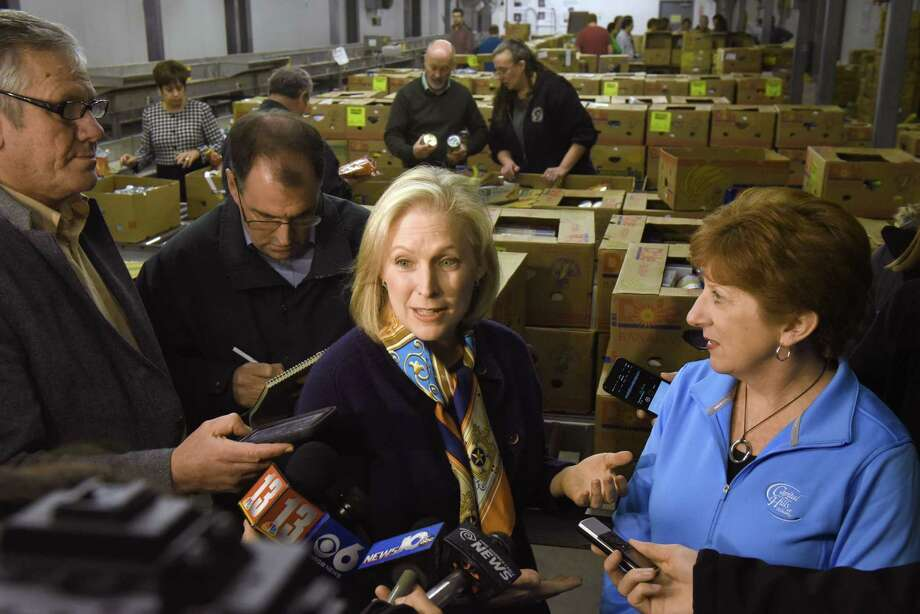 U.S. Senator Kirsten Gillibrand, center, endorses Albany Mayor Kathy Sheehan, right, for her mayoral run during a break in volunteering at the Regional Food Bank of Northeastern New York on Friday, Dec. 2, 2016, in Colonie, N.Y.  (Michael P. Farrell/Times Union) Photo: Michael P. Farrell / 20039032A