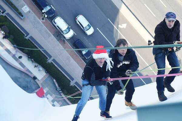Brian Cashman, General Manager for the Yankees, Rick Reichmuth of Fox News, center, and Brian VanOrsdel prepare for the DSSD's annual Rappelling Santa and Holiday Tree Lighting event with a practice run from the top of the Landmark Square building in Stamford, Conn., Dec. 2, 2016. Cashman has been filling the role of Santa for five years, starting with the rappel from one of the state's tallest building followed by a parade to Lapham Park and a tree lighting ceremony. The event will take place Sunday, Dec. 8 at 5 PM.
