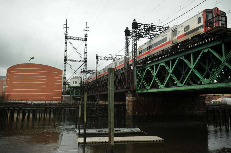 A Metro-North train heading east crosses the Walk Bridge over the Norwalk River in Norwalk, Conn. on Tuesday, April 12, 2016. The bridge, which bisects the Norwalk Aquarium, at left, is scheduled to be replaced. Photo: Brian A. Pounds / Hearst Connecticut Media / Connecticut Post