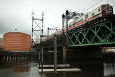 A Metro-North train heading east crosses the Walk Bridge over the Norwalk River in Norwalk, Conn. on Tuesday, April 12, 2016. The bridge, which bisects the Norwalk Aquarium, at left, is scheduled to be replaced.