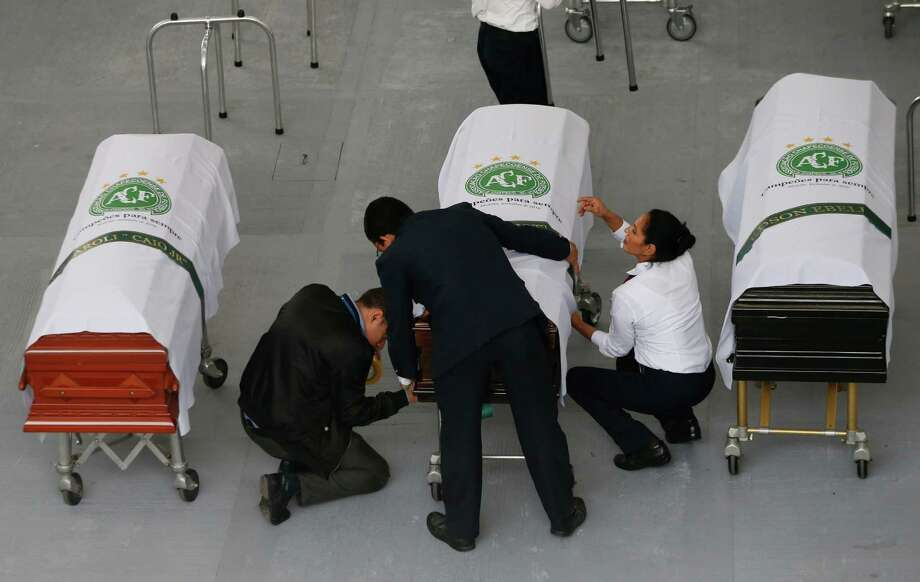Funeral employees wrap an identification label around a casket covered in a white sheet with a Chapecoense soccer team logo that contains the remains of a team member at the San Vicente funeral home in Medellin, Colombia, Friday, Dec. 2, 2016. The bodies of the Brazilian victims of this week's air tragedy will be repatriated later Friday on three flights to Chapeco, the hometown of the Brazilian soccer team. Members of the team and a group of journalists who perished on the flight were headed to the Copa Sudamericana finals when the plane ran out of fuel, crashing into the Andes outside Medellin. (AP Photo/Fernando Vergara) Photo: Fernando Vergara, STF / Copyright 2016 The Associated Press. All rights reserved.
