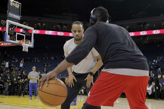 Rockets assistant coach Irving Roland, left, works with James Harden (13) before the Houston Rockets played the Golden State Warriors at Oracle Arena in Oakland, Calif., on Thursday, December 1, 2016.