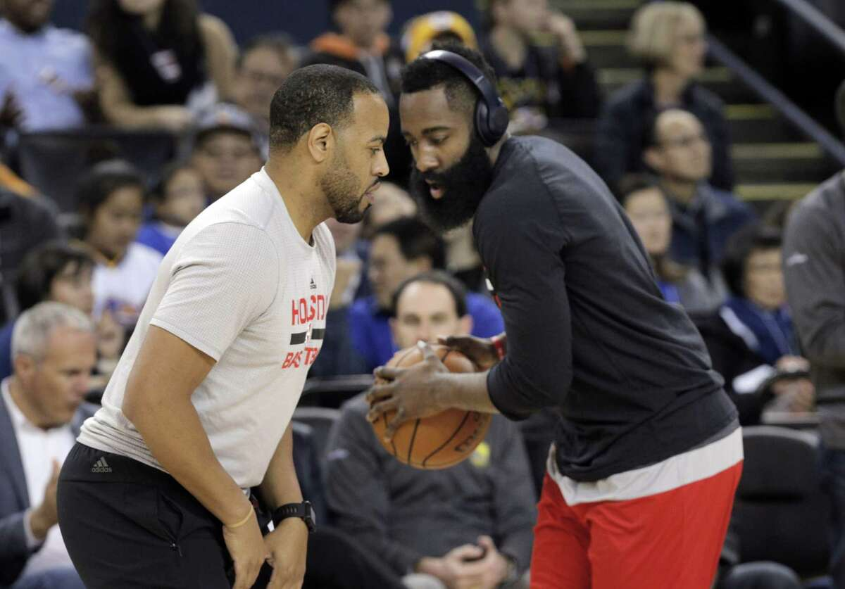 Irving Roland, left, works with James Harden (13) before the Houston Rockets played the Golden State Warriors at Oracle Arena in Oakland, Calif., on Thursday, December 1, 2016.