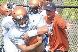 Western Connecticut State running back Mike Nichol, left, takes a handoff from running backs coach Chuck Lynch during practice Aug. 16, 2016.