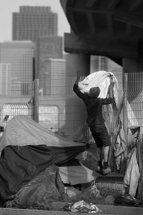 Lionel Gadson makes adjistments to his tent structure along 7th Street in San Francisco. Photo: Lea Suzuki, The Chronicle