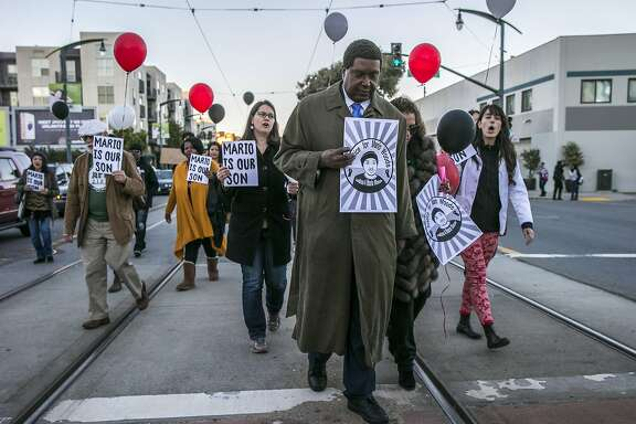 Center: Civil rights lawyer John Burris march along 3rd Street during an event commemorating the one-year anniversary of Mario Woods' death, Friday, Dec. 2, 2016 in San Francisco, Calif.