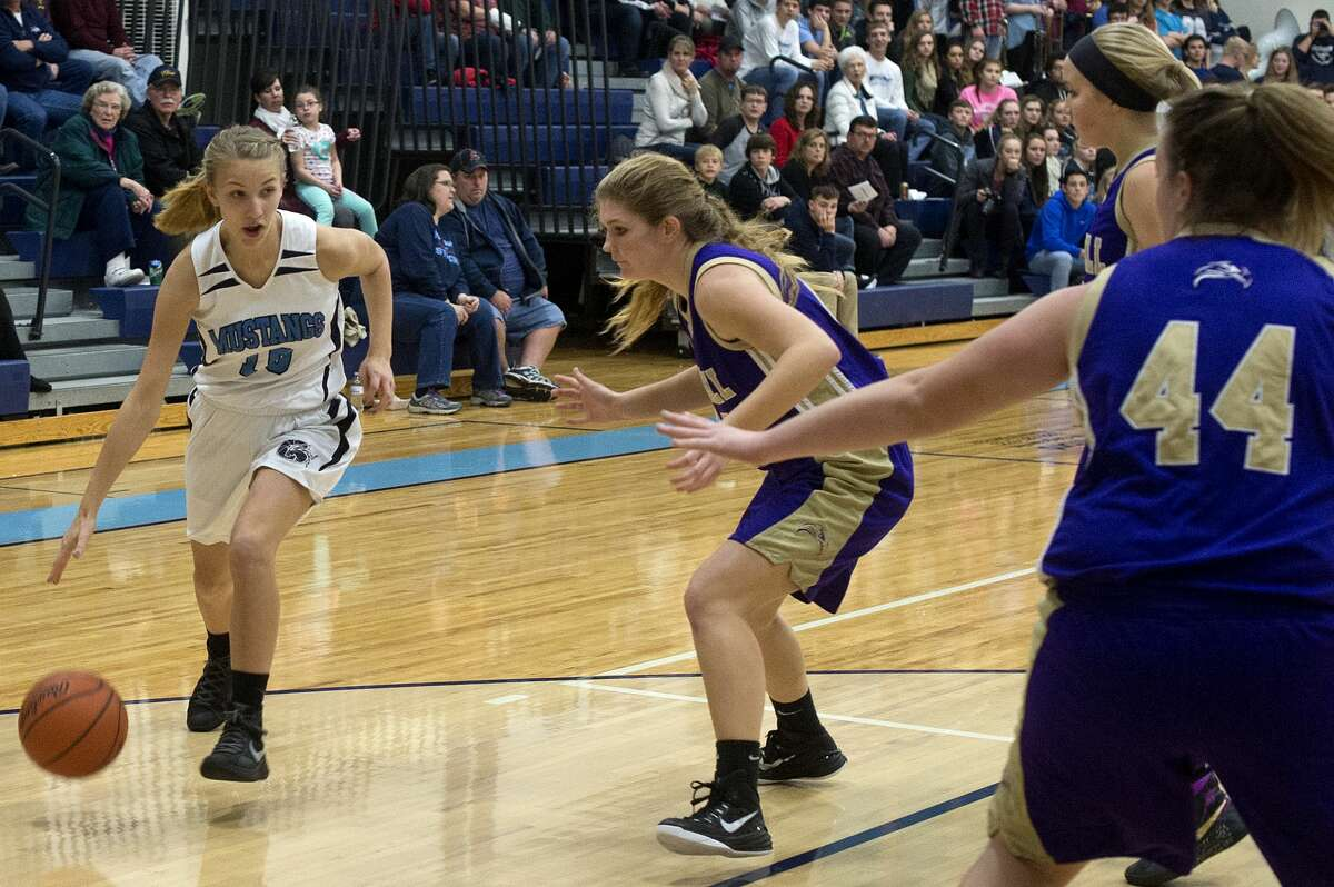 Meridian's Camryn McKellar dribbles around Farwell's Grace Saupe in the first half of Friday's game.