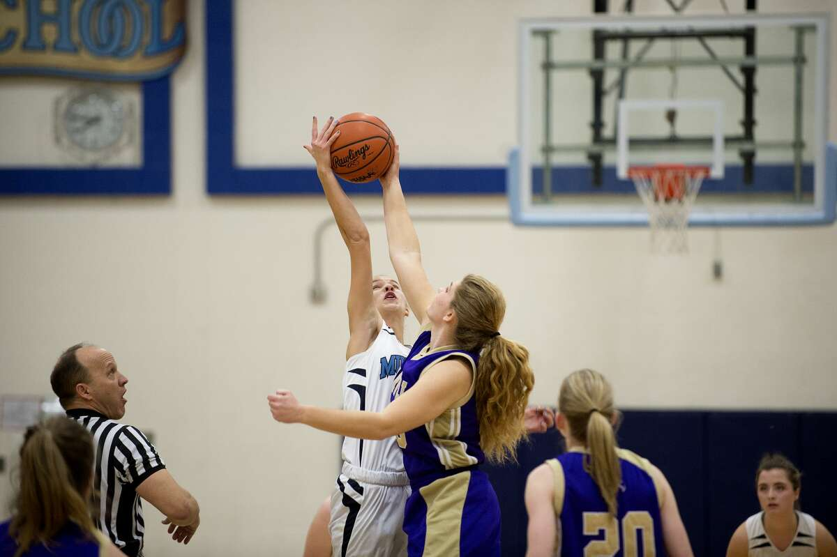 Meridian's Camryn McKellar and Farwell's Grace Saupe tip off in the first half of Friday's game.