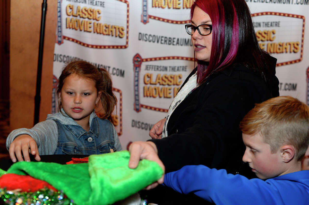 Tallyn Meek, 8, Shaun Meek and Christopher Hart, 8, pick out props for the photo booth before the showing of