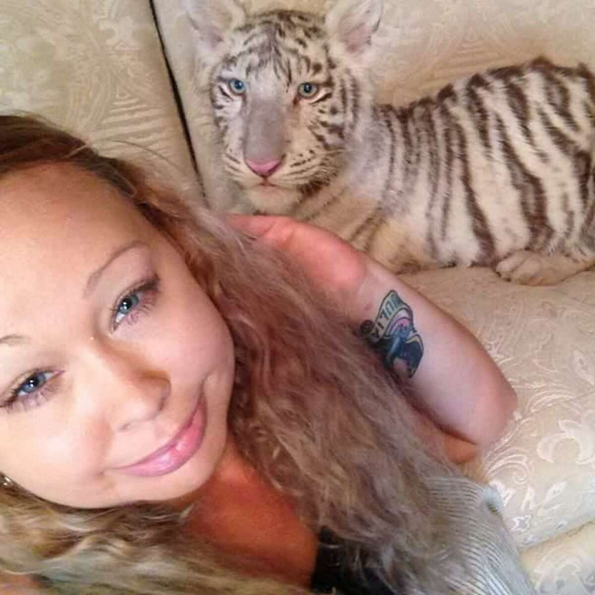 Trisha Meyer poses for a selfie with a white tiger. Meyer has been accused with child endangerment for allegedly letting her animals run free in the house with her daughter.