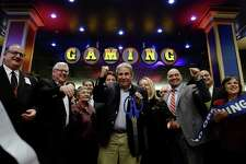 Jeff Gural, center, owner of Tioga Downs, cuts a ribbon during the official opening ceremony for the casino's new gaming floor and poker room Friday, Dec. 2, 2016, in Nichols, N.Y. The first of four planned casinos opened with a flurry of balloons, confetti and uncertain visions of economic resurgence on Friday as New York ushered in a new era of state-sanctioned gambling aimed at reversing decades of upstate decline. (AP Photo/Heather Ainsworth) ORG XMIT: NYHA204