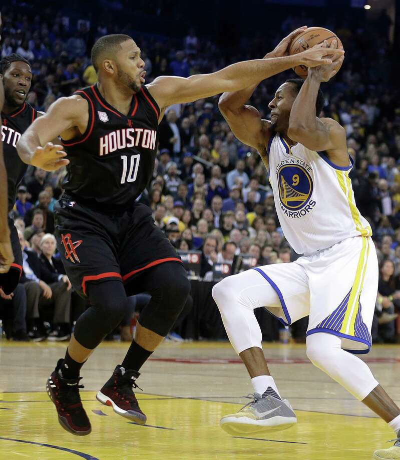 Eric Gordon, left, plays some sticky defense against the Warriors' Andre Iguodala during the Rockets' double-overtime victory Thursday night. Photo: Ben Margot, STF / Copyright 2016 The Associated Press. All rights reserved.
