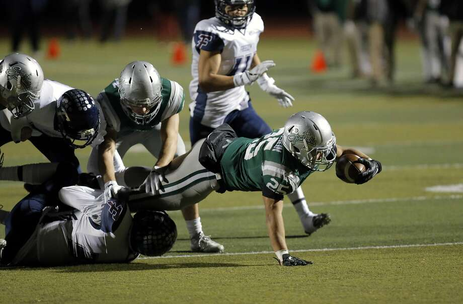 Spartans Kairee Robinson, 25 stretches for a first quarter first down,as De La Salle-Concord  takes on Freedom in the North Ooast section open division football championship at  Dublin hIgh school in Dublin, California, on Friday December 2, 2016. Photo: Michael Macor, The Chronicle