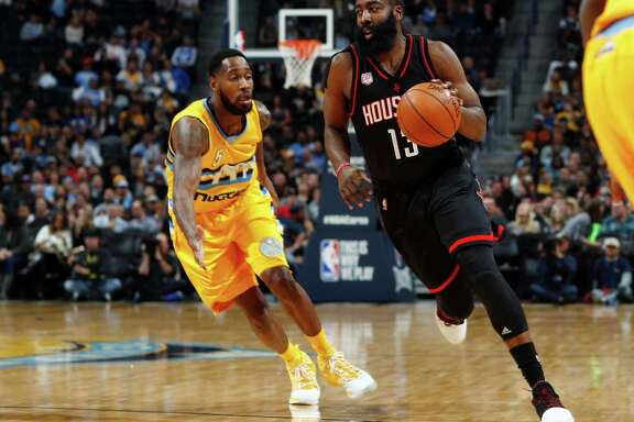 Houston Rockets guard James Harden, right, drives past Denver Nuggets guard Will Barton in the first half of an NBA basketball game late Friday, Dec. 2, 2016, in Denver. (AP Photo/David Zalubowski)