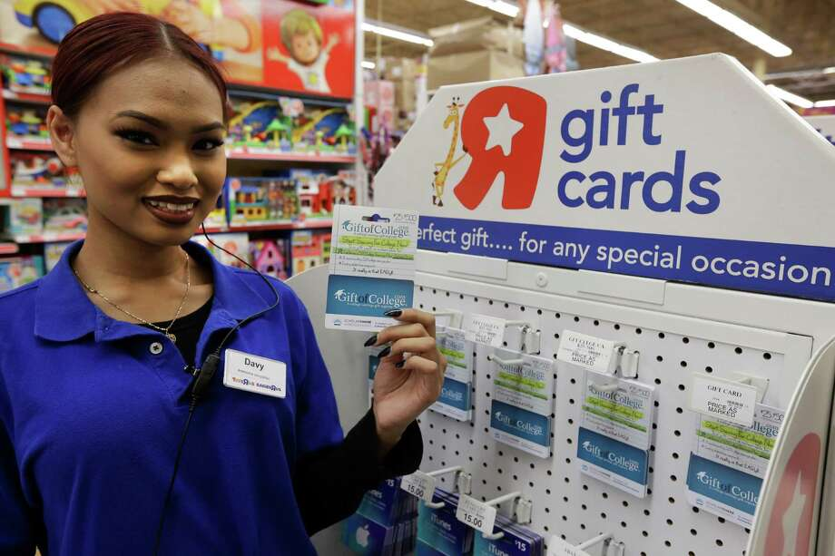 Toys R Us employee Davy Pen displays a Gift of College gift card in Emeryville, Calif. Gift of College helps people to contribute to college savings plans or pay down student loans.  Photo: Ben Margot, STF / Copyright 2016 The Associated Press. All rights reserved.