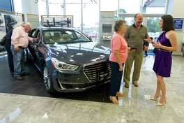 Falon Wiesner-Jones, director of public relations for Wiesner, visits with Horst and Dagmar Moehrke beside the Genesis G90 during the unveiling of the new Genesis line of luxury cars at Wiesner Hyundai Tuesday, Nov. 29, 2016, in Conroe.