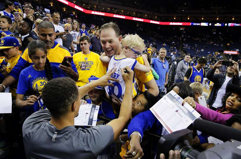 Greg Bell of Danville, holds his son Charlie, 5, up for Stephen Curry (30) to sign his jersey during warmups before the Warriors played the Portland Trail Blazers during a pre-season game at Oracle Arena in Oakland, Calif., on Friday, October 21, 2016. The Warriors won 107-96. Photo: Carlos Avila Gonzalez, The Chronicle
