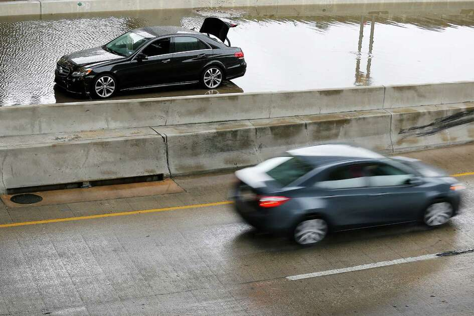 A vehicle appears abandoned along I-10 and Culebra after rains flood a portion of the lower level of the highway on Saturday, Dec. 3, 2016. Weather forecasts have called for continued rain storms in the area through the weekend.