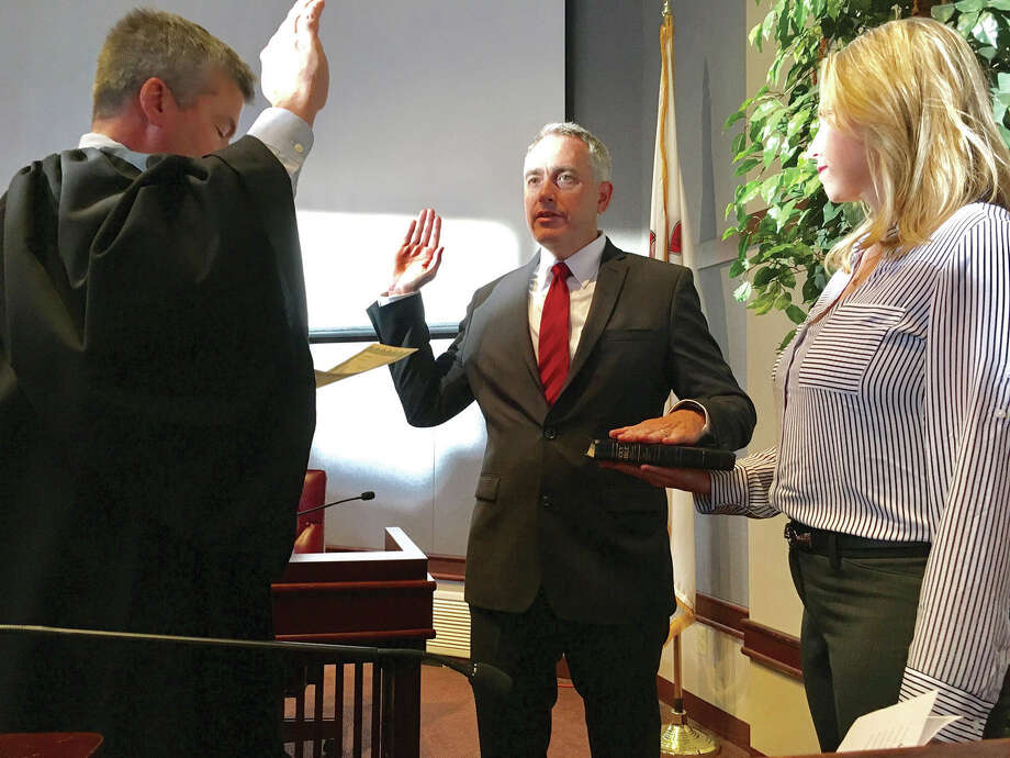 Madison County State's Attorney Tom Gibbons, center, is sworn in by Judge William Mudge. At right is Gibbons' wife Lori. Photo: Steve Horrell • Shorrell@edwpub.net