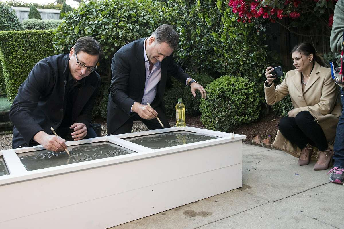 """""""Full House"""" cast members Bob Saget and Dave Coulier write their names in cement as Coulier's wife Melissa Coulier (left to right) snaps a photo in the backyard of the property used in the sitcom as the home of the fictional Tanner family during press event for the second season of the Netflix sequel """"Fuller House"""" in San Francisco, Calif., on Friday, December 2, 2016. """"Full House"""" creator Jeff Franklin recently purchased the property."""