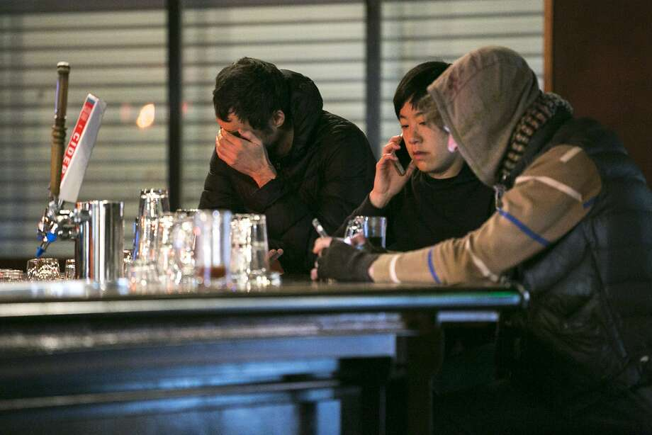 Jenny Yang (center) and others at Eli's Mile High Club bar try to find more information about their friends, on Saturday, Dec. 3, 2016, who attended a warehouse party in Oakland, Calif., that caught on fire. At least nine people were killed in a warehouse party fire at 31st Avenue and International Boulevard, in the Fruitvale neighborhood. As many as 100 people were inside for a performance by the Golden Donna 100 Percent Silk touring electronic dance music show. Photo: Santiago Mejia, The Chronicle